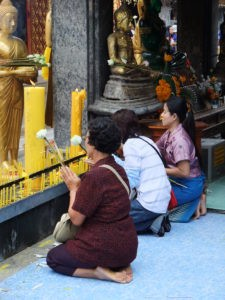 Lay-people visiting a temple in Thailand on Buddha Day make offerings.
