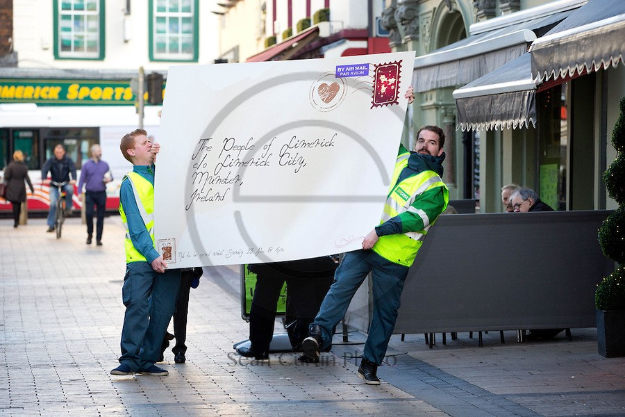 """Amy Walsh, Caherdavin Limerick watch as Postmen Ciaran Collins and Kevin Kiely by the massive Christmas card they are delivering for the people of Limerick ahead of switching on of the city's Christmas lights this Sunday. The card is to be opened at a special event that will see airborne Santa's elves decorate the city's Christmas Tree on Bedford Row at 4pm on Sunday 23rd November. Official news from the North Pole is just in. Limerick has come in top of class on the 'good' list! This year the council of nice is diverting funds to Limerick to spend on extra magic, extra joy and extra spirit. We don't know if it was the elves or the fairies, but somebody spilled the magic dust all over Limerick and the city is lighting up in all sorts of unexpected magical ways… and it all kicks off this Sunday when the people of Limerick are delivered a Christmas message like never before. Ahead of the much anticipated switching on of the Christmas in Limerick festive lights, a GIANT envelope (which is 2 meters tall!) has been delivered addressed to """"The People of Limerick""""… with a special note that it is not to be opened until Sunday 23 November at 4pm. Although the identity of the sender is still unconfirmed, we've a BIG hunch we know who it is from, so we've drafted in a very special translator to join us on Bedford Row this coming Sunday to help us open it… Pic Sean Curtin Photo."""