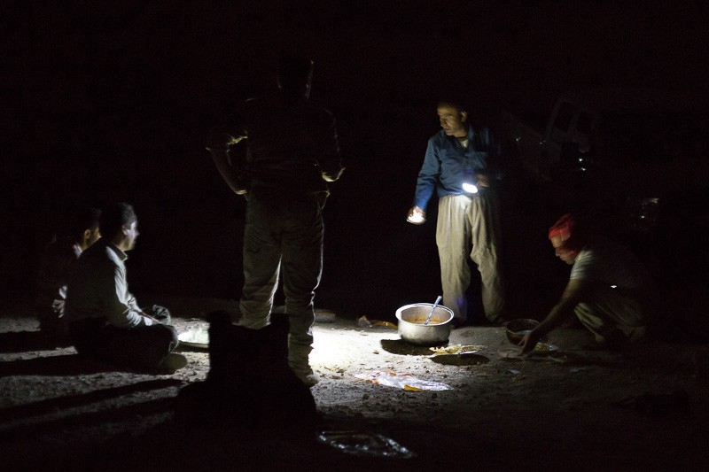 01/09/2015. Bashiqa, Iraq. Kurdish peshmerga make dinner by torchlight at a defensive position on Bashiqa Mountain, Iraq. Bashiqa Mountain, towering over the town of the same name, is now a heavily fortified front line. Kurdish peshmerga, having withdrawn to the mountain after the August 2014 ISIS offensive, now watch over Islamic State held territory from their sandbagged high-ground positions. Regular exchanges of fire take place between the Kurds and the Islamic militants with the occupied Iraqi city of Mosul forming the backdrop. The town of Bashiqa, a formerly mixed town that had a population of Yazidi, Kurd, Arab and Shabak, now lies empty apart from insurgents. Along with several other urban sprawls the town forms one of the gateways to Iraq's second largest city that will need to be dealt with should the Kurds be called to advance on Mosul.