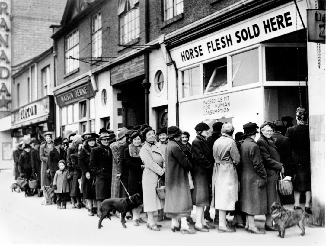 Women line up outside a butcher shop in North Cheam, Surrey, England to buy scarce meat (was in short-supply and heavily rationed during the war) during World War II. (AP Photo)
