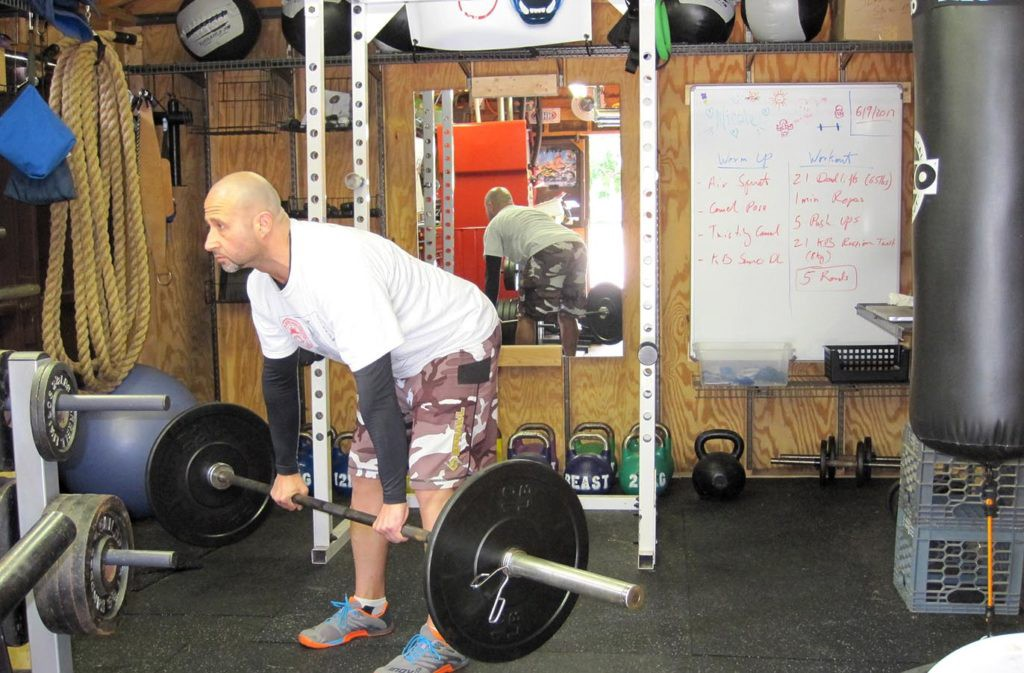 man bent over with flat back arms straight holding barbell off the ground in a straight leg deadlift