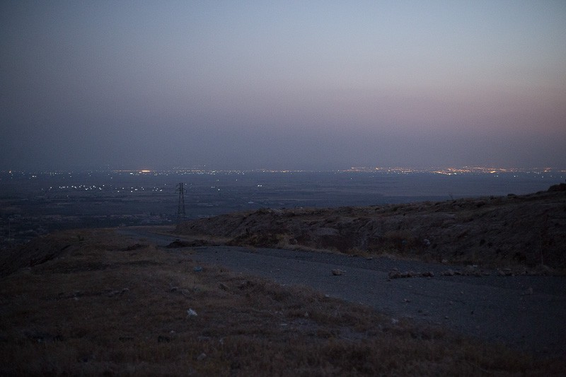 01/09/2015. Bashiqa, Iraq. Lights coming from Islamic State held Mosul, Iraq's second largest city, are seen from Kurdish peshmerga defensive positions on Bashiqa Mountain. Bashiqa Mountain, towering over the town of the same name, is now a heavily fortified front line. Kurdish peshmerga, having withdrawn to the mountain after the August 2014 ISIS offensive, now watch over Islamic State held territory from their sandbagged high-ground positions. Regular exchanges of fire take place between the Kurds and the Islamic militants with the occupied Iraqi city of Mosul forming the backdrop. The town of Bashiqa, a formerly mixed town that had a population of Yazidi, Kurd, Arab and Shabak, now lies empty apart from insurgents. Along with several other urban sprawls the town forms one of the gateways to Iraq's second largest city that will need to be dealt with should the Kurds be called to advance on Mosul.