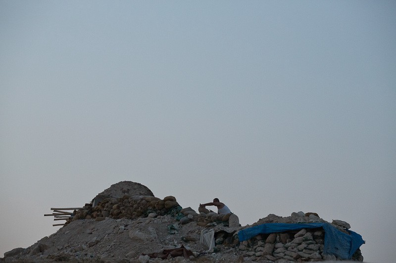01/09/2015. Bashiqa, Iraq. A Kurdish peshmerga fighter uses sandbags to reinforce a defensive position on the top of Bashiqa Mountain, Iraq. Bashiqa Mountain, towering over the town of the same name, is now a heavily fortified front line. Kurdish peshmerga, having withdrawn to the mountain after the August 2014 ISIS offensive, now watch over Islamic State held territory from their sandbagged high-ground positions. Regular exchanges of fire take place between the Kurds and the Islamic militants with the occupied Iraqi city of Mosul forming the backdrop. The town of Bashiqa, a formerly mixed town that had a population of Yazidi, Kurd, Arab and Shabak, now lies empty apart from insurgents. Along with several other urban sprawls the town forms one of the gateways to Iraq's second largest city that will need to be dealt with should the Kurds be called to advance on Mosul.