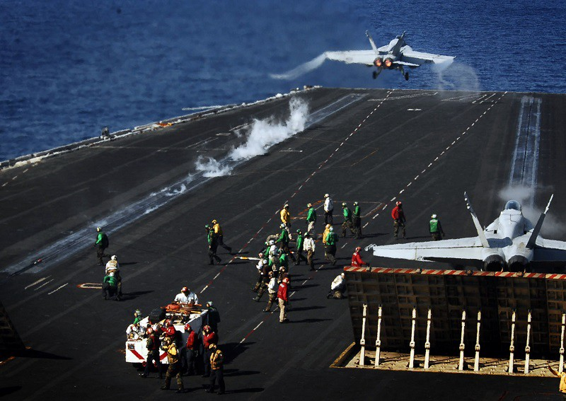 "An F/A-18E Super Hornet from the ""Argonauts"" of Strike Fighter Squadron 14 (left) launches, while an F/A-18C from the ""Death Rattlers"" of Marine Strike Squadron 323 prepares to launch from the flight deck of the Nimitz-class aircraft carrier USS John C. Stennis. Stennis and Carrier Air Wing 9, as part of John C. Stennis Carrier Strike Group, are conducting a composite training unit exercise off the coast of southern California."