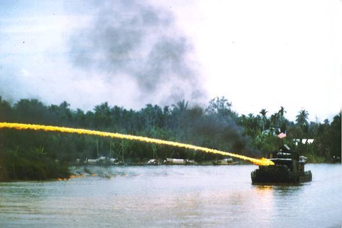 A flame-thrower equipped monitor blasts a riverbank Vietnam. Navy photo