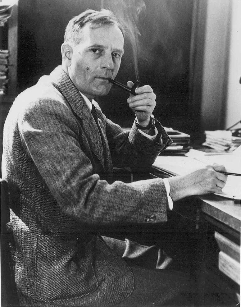 Edwin Hubble sitting at a desk with a pipe