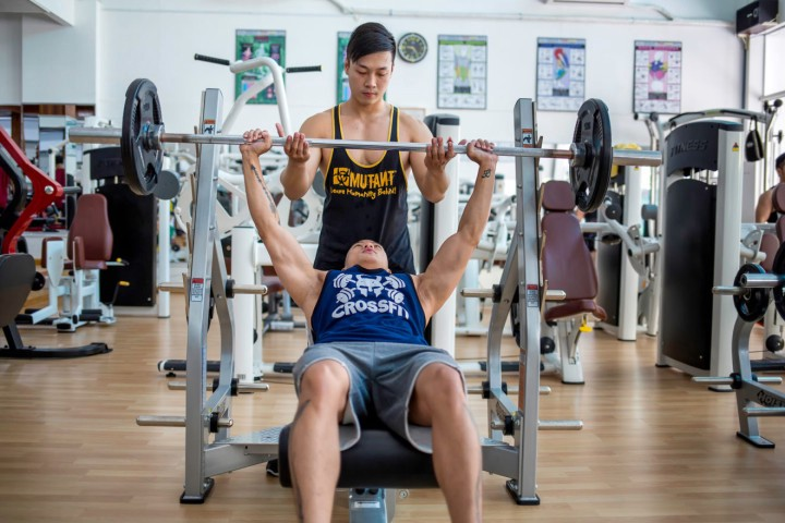Kendy lifts weights with a trainer.