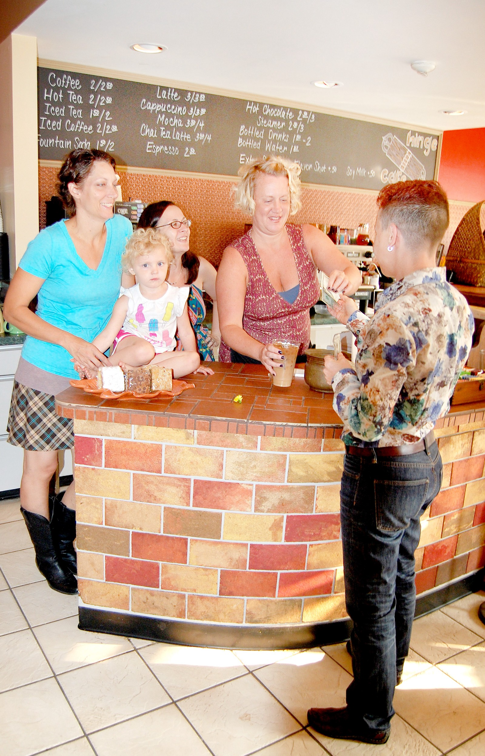from left hinge caf proprietor simone her daughter cyan and staff members jill therrien and bridgette sullivan serve an iced coffee to the first - Cyan Cafe Interior