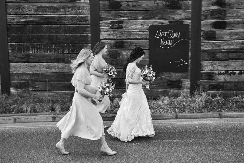 wedding regrets - bridesmaids and bride walking along street in black and white