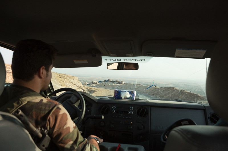 01/09/2015. Bashiqa, Iraq. Islamic State held Iraq is seen beyond Kurdish peshmerga positions through the windscreen of a peshmerga off road vehicle. Bashiqa Mountain, towering over the town of the same name, is now a heavily fortified front line. Kurdish peshmerga, having withdrawn to the mountain after the August 2014 ISIS offensive, now watch over Islamic State held territory from their sandbagged high-ground positions. Regular exchanges of fire take place between the Kurds and the Islamic militants with the occupied Iraqi city of Mosul forming the backdrop. The town of Bashiqa, a formerly mixed town that had a population of Yazidi, Kurd, Arab and Shabak, now lies empty apart from insurgents. Along with several other urban sprawls the town forms one of the gateways to Iraq's second largest city that will need to be dealt with should the Kurds be called to advance on Mosul.