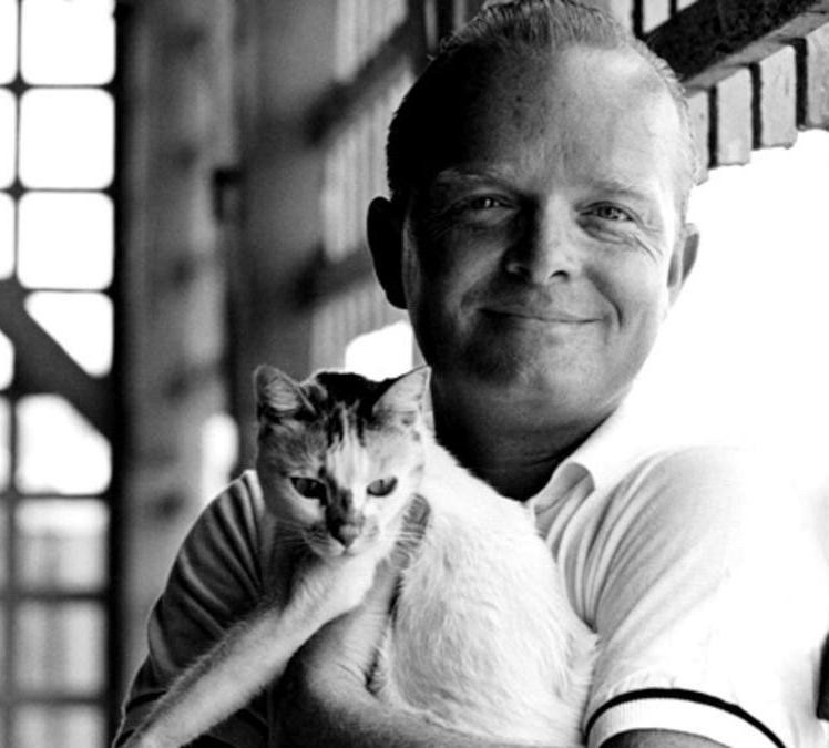 Truman Capote smiling with holding a cat