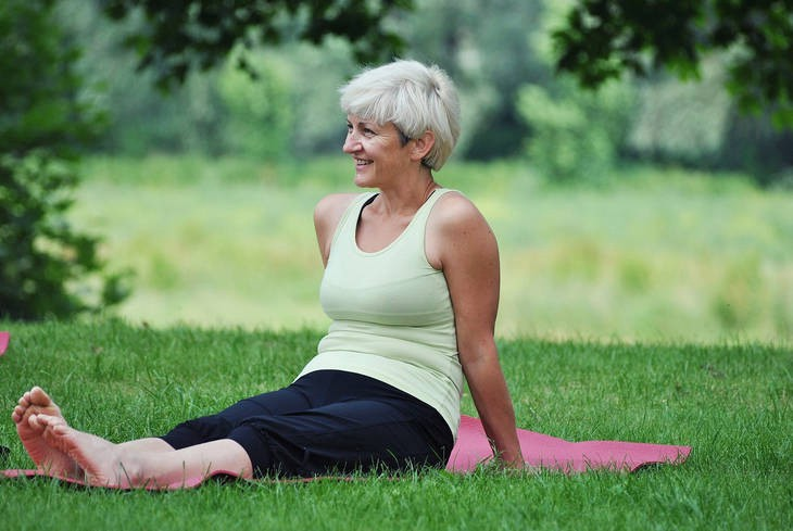 Middle-aged woman sitting on yoga mat - Yoga over 50