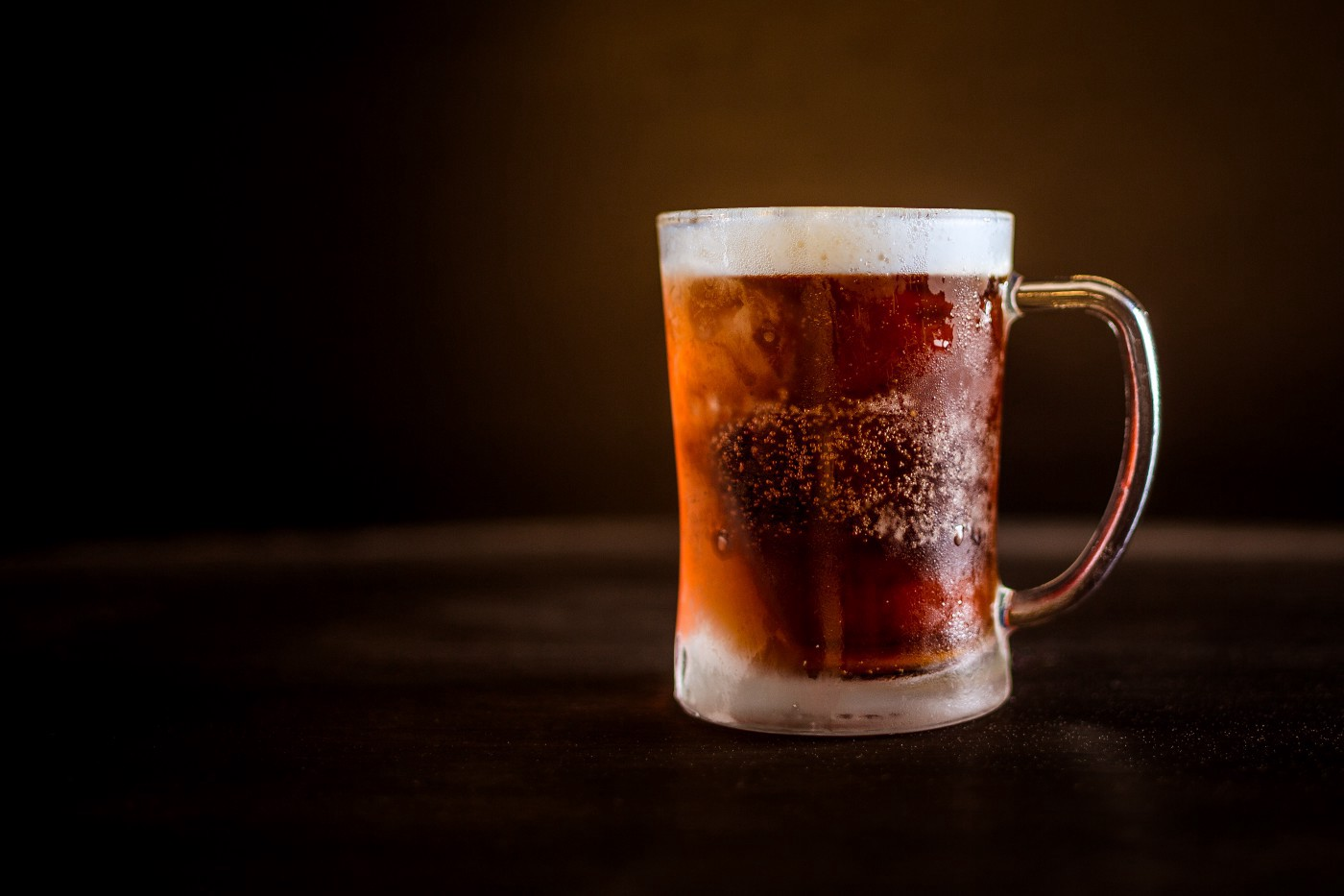 A mug full of beer sits on a wooden bar.