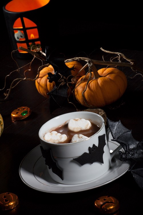 spiked hot chocolate with ghost marshmallow, surrounded with pumpkins, candles, and Halloween decoration. Halloween drinks series.