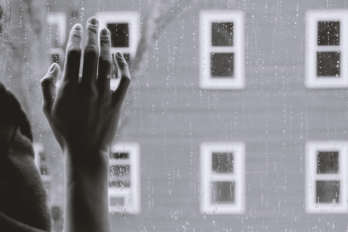 A person holds their hand against a rainy window looking out at another building.