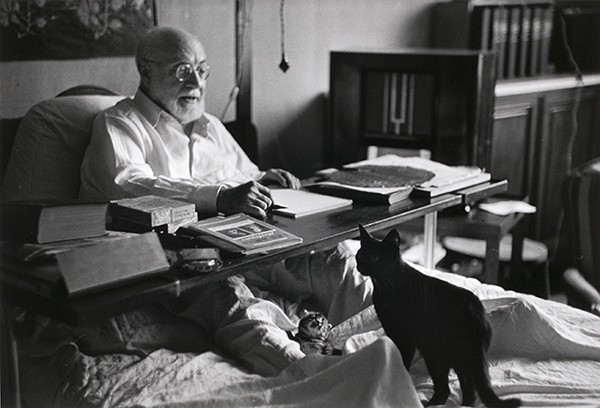 Henri Matisse and his cat in bed