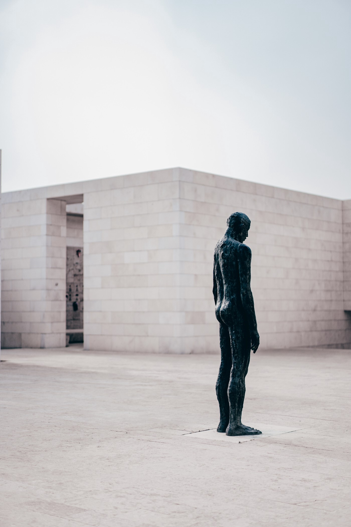 A statue of a human figure stands alone in a courtyard built from stone blocks.