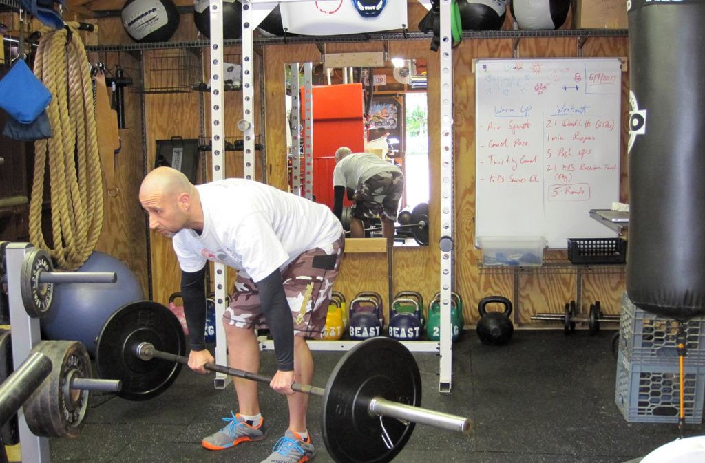 man holding barbell bent over in the middle of a deadlift
