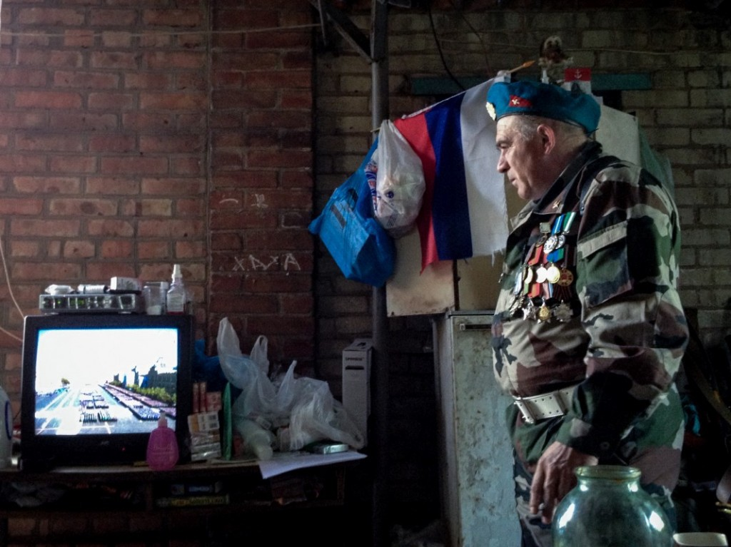 Yuri, a rebel commander, watches a Victory Day parade at his base in Slovyansk, Ukraine (Noah Sneider)