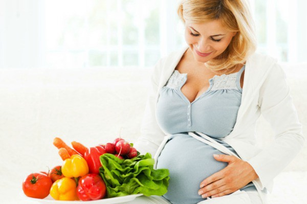 Cheerful beautiful pregnant woman sitting on the sofa with a bowl full of vegetables.