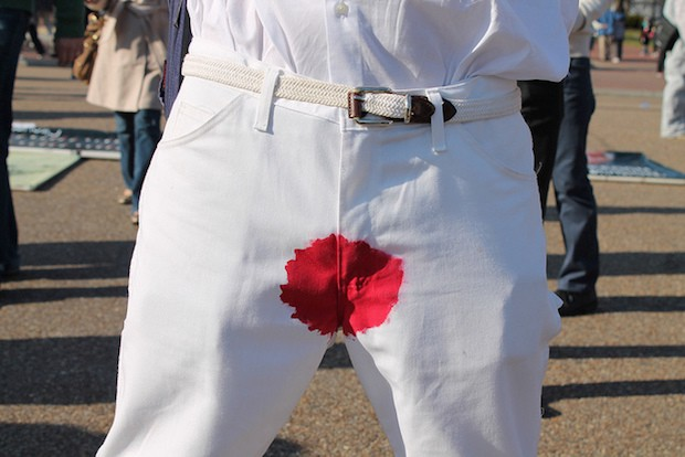 An intactivist protestor wears pants stained with fake blood