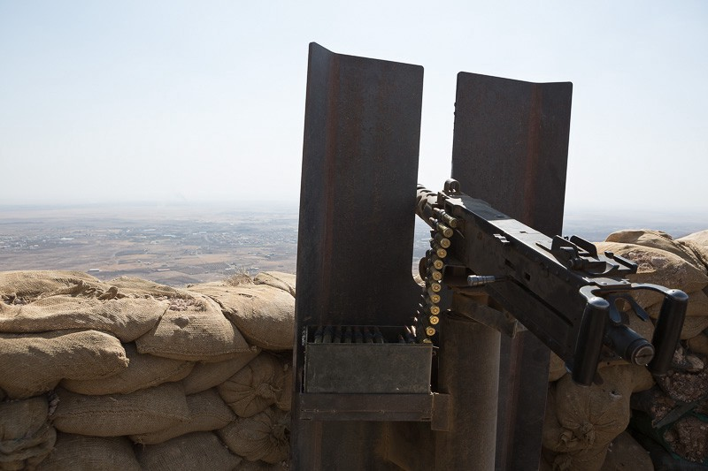 01/09/2015. Bashiqa, Iraq. An American made .50 caliber Browning heavy machine gun, donated by coalition forces, is seen at a peshmerga position on Bashiqa mountain near Mosul, Iraq. Bashiqa Mountain, towering over the town of the same name, is now a heavily fortified front line. Kurdish peshmerga, having withdrawn to the mountain after the August 2014 ISIS offensive, now watch over Islamic State held territory from their sandbagged high-ground positions. Regular exchanges of fire take place between the Kurds and the Islamic militants with the occupied Iraqi city of Mosul forming the backdrop. The town of Bashiqa, a formerly mixed town that had a population of Yazidi, Kurd, Arab and Shabak, now lies empty apart from insurgents. Along with several other urban sprawls the town forms one of the gateways to Iraq's second largest city that will need to be dealt with should the Kurds be called to advance on Mosul.