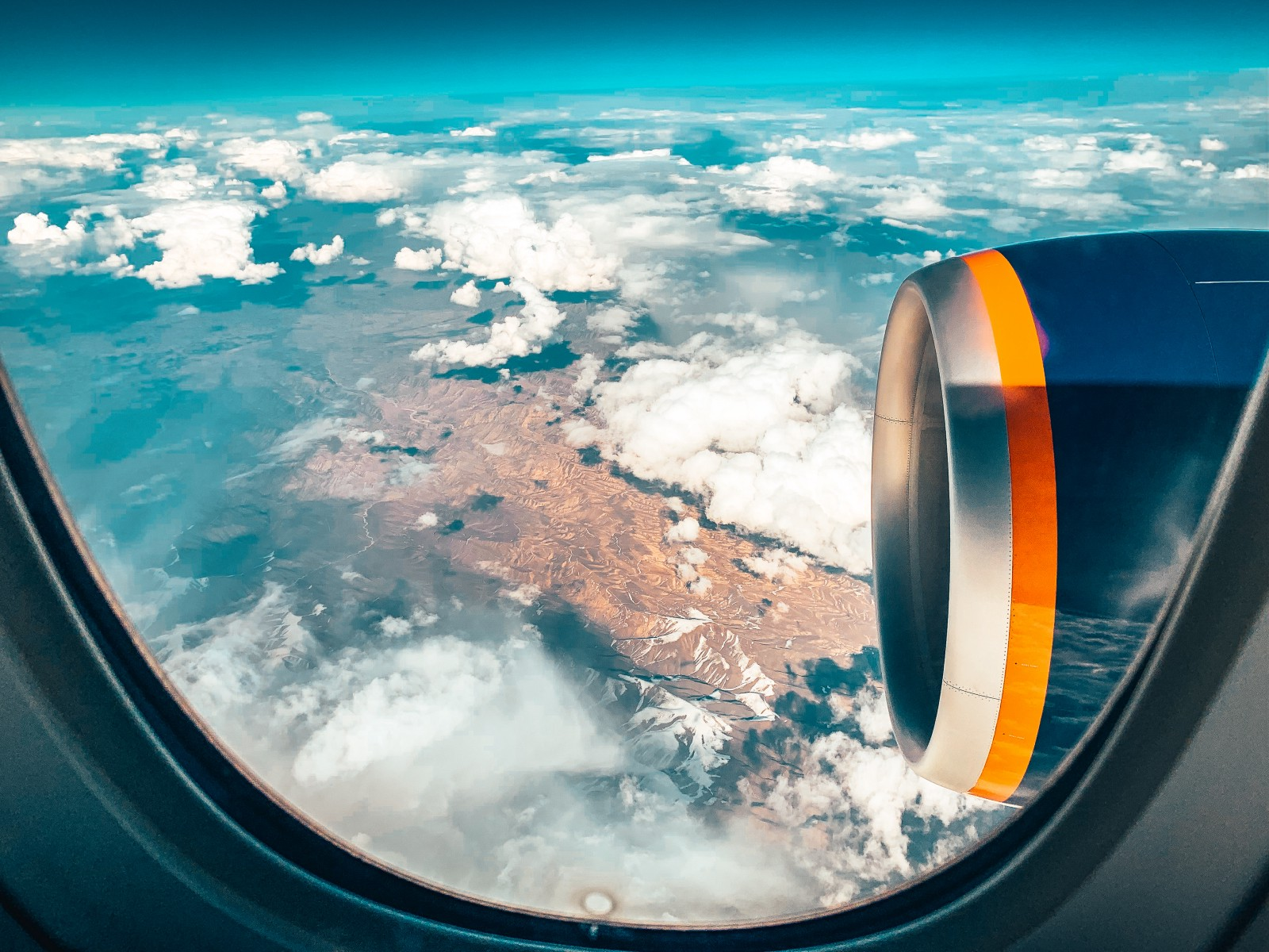 A jet engine and clouds photographed from inside and airplane.