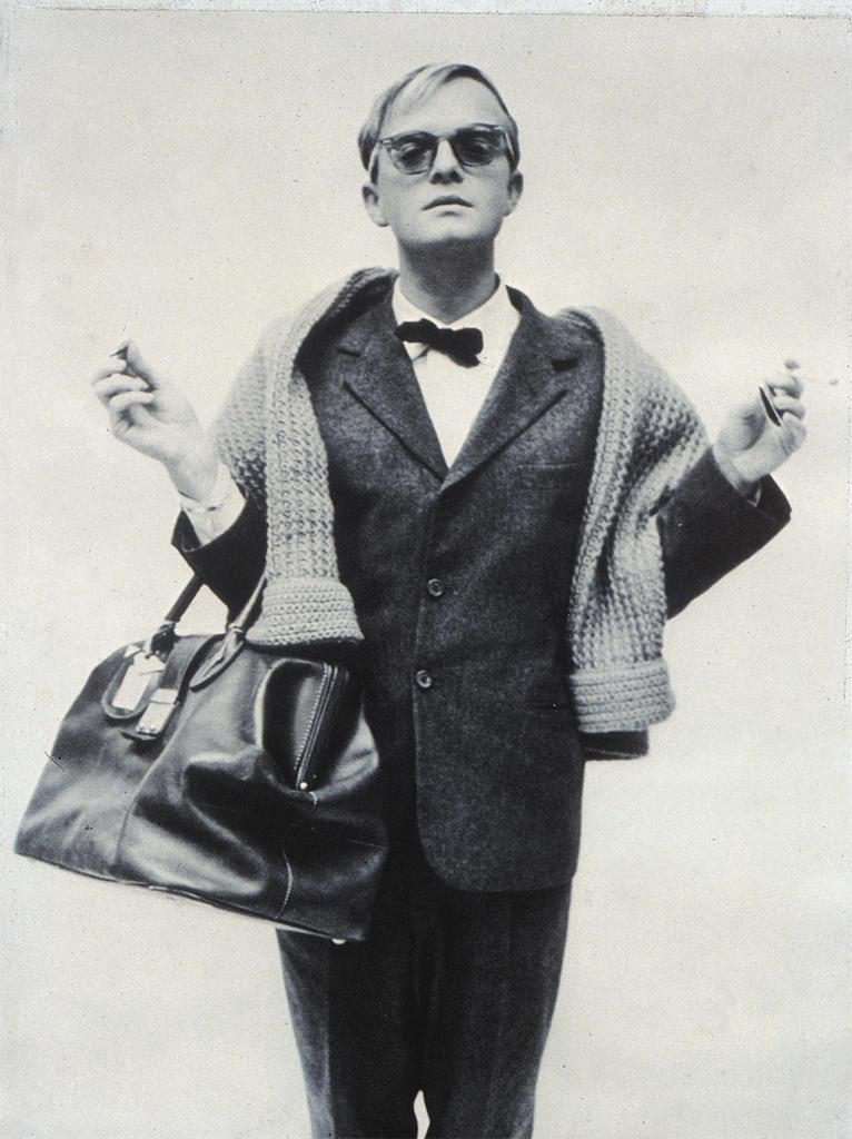 Truman Capote with a jacket, a tie and a weekender bag