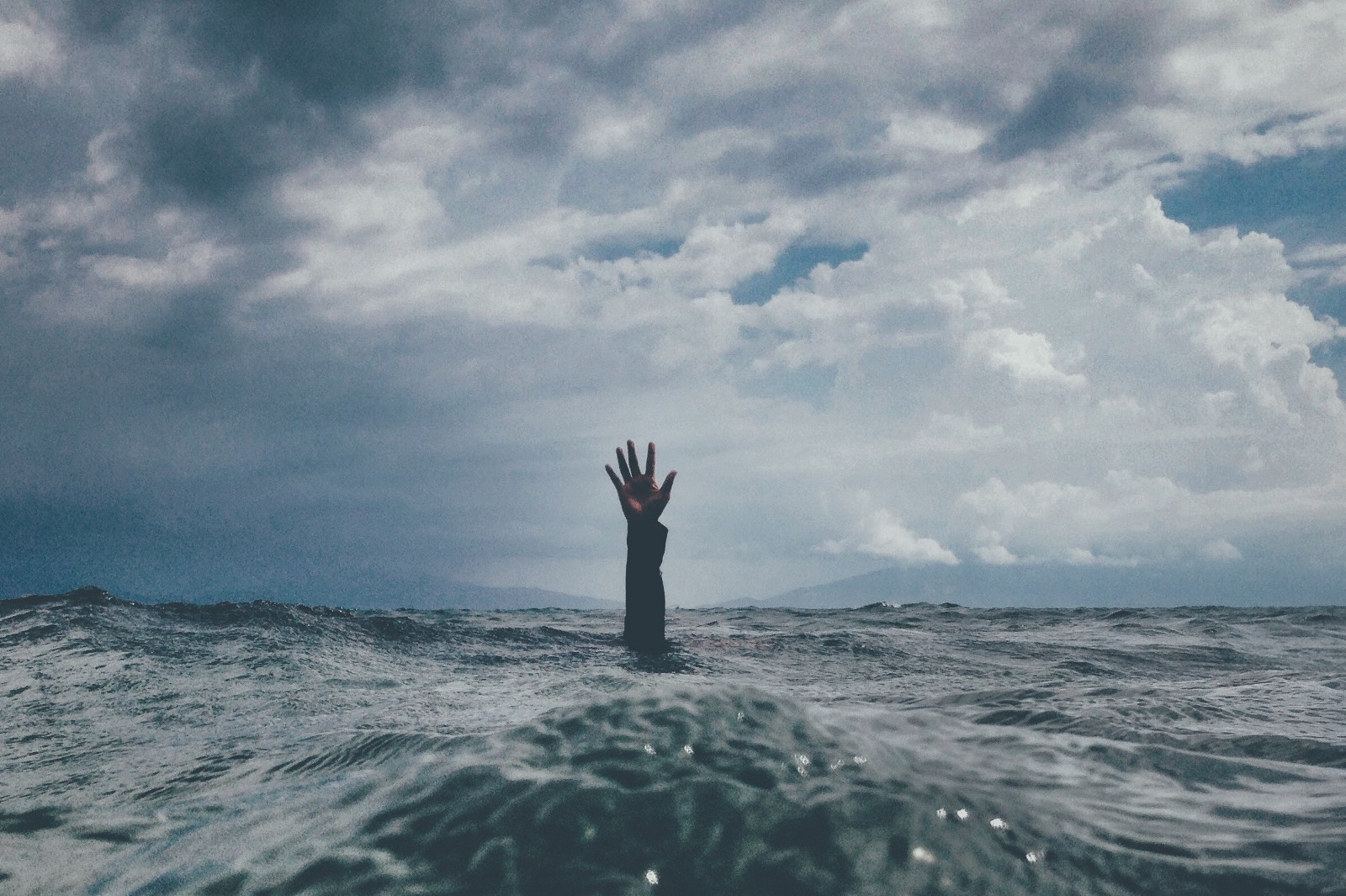 person at sea drowning with arms above water