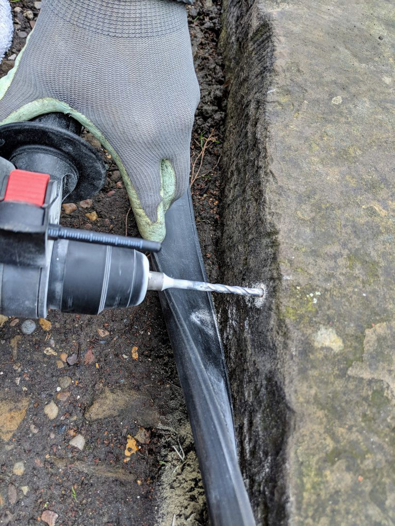 Taking care not to damage the rubber trim while drilling.