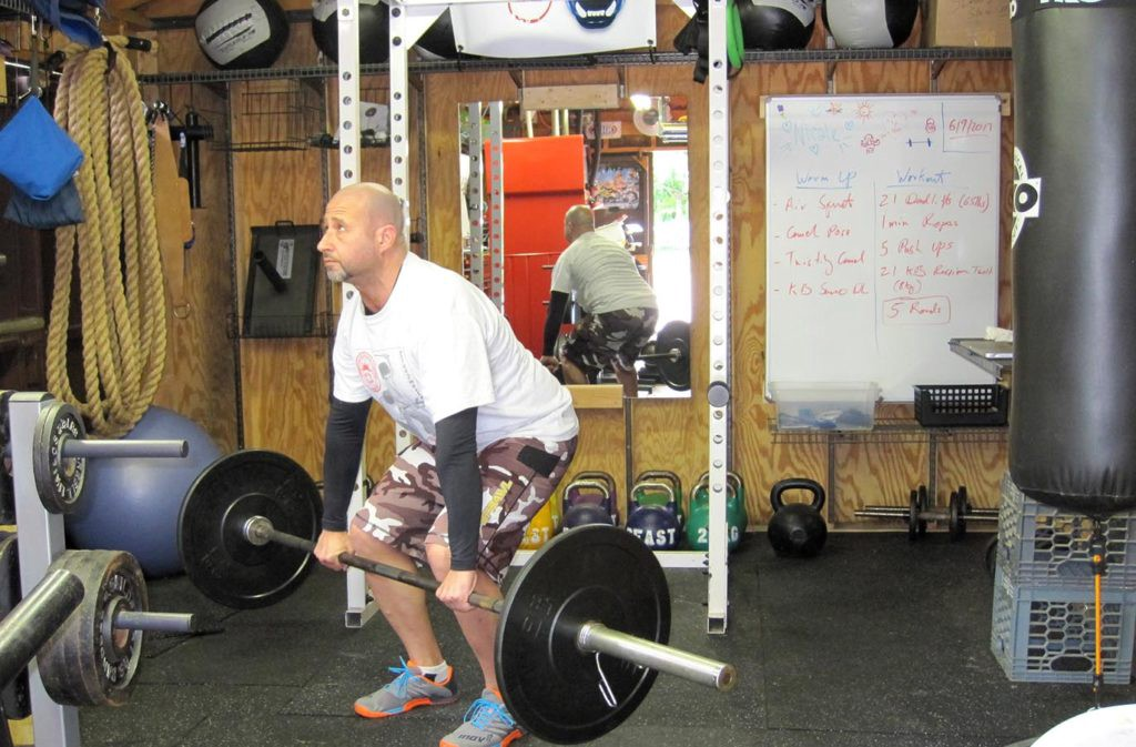 man holding barbell in the middle of a deadlift