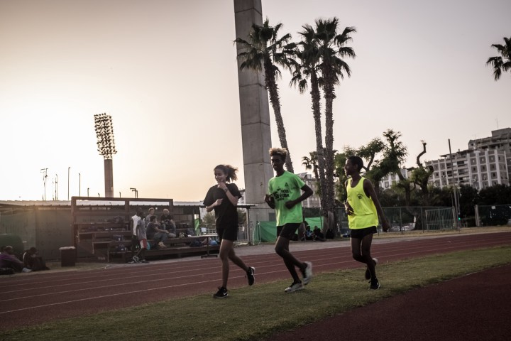 Eritrean asylum seeker and athlete Rahel (left) trains with other young male teammates at the National Sport Center Stadium in Tel Aviv (Israel), as she became too fast to train with the rest of the girls and beats many of the boys as well.