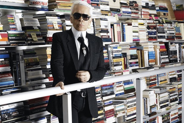 Karl Lagerfeld standing in front of book shelves