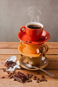 Coffee cup with chocolate on wooden table