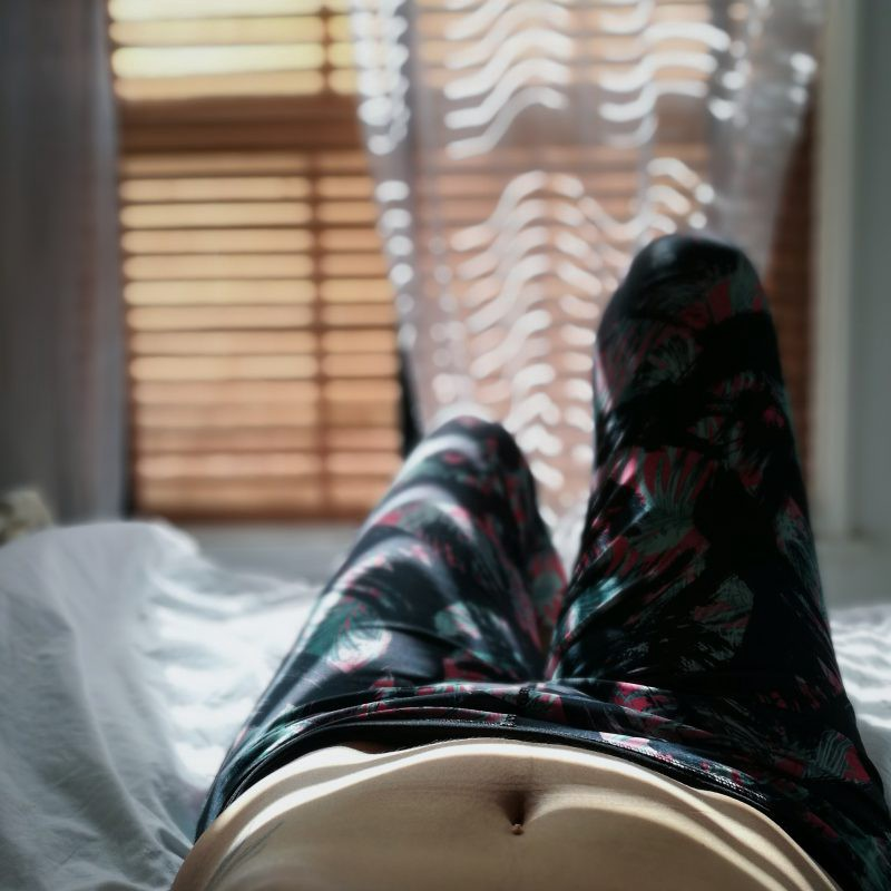 womans legs on bed in afternoon light