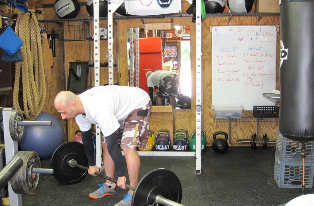 man bent over with flat back arms straight with hands clasping barbell