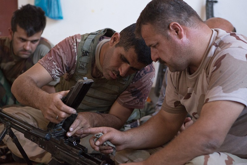 01/09/2015. Bashiqa, Iraq. Two Kurdish peshmerga fighters clean an M84 general purpose machine gun during downtime at a peshmerga position on Bashiqa Mountain near Mosul. Bashiqa Mountain, towering over the town of the same name, is now a heavily fortified front line. Kurdish peshmerga, having withdrawn to the mountain after the August 2014 ISIS offensive, now watch over Islamic State held territory from their sandbagged high-ground positions. Regular exchanges of fire take place between the Kurds and the Islamic militants with the occupied Iraqi city of Mosul forming the backdrop. The town of Bashiqa, a formerly mixed town that had a population of Yazidi, Kurd, Arab and Shabak, now lies empty apart from insurgents. Along with several other urban sprawls the town forms one of the gateways to Iraq's second largest city that will need to be dealt with should the Kurds be called to advance on Mosul.