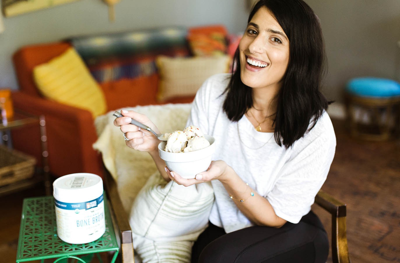 attractive woman smiling holding a bowl of guilt-free cake batter bone broth n'ice cream beside a container of natural force vanilla organic bone broth protein