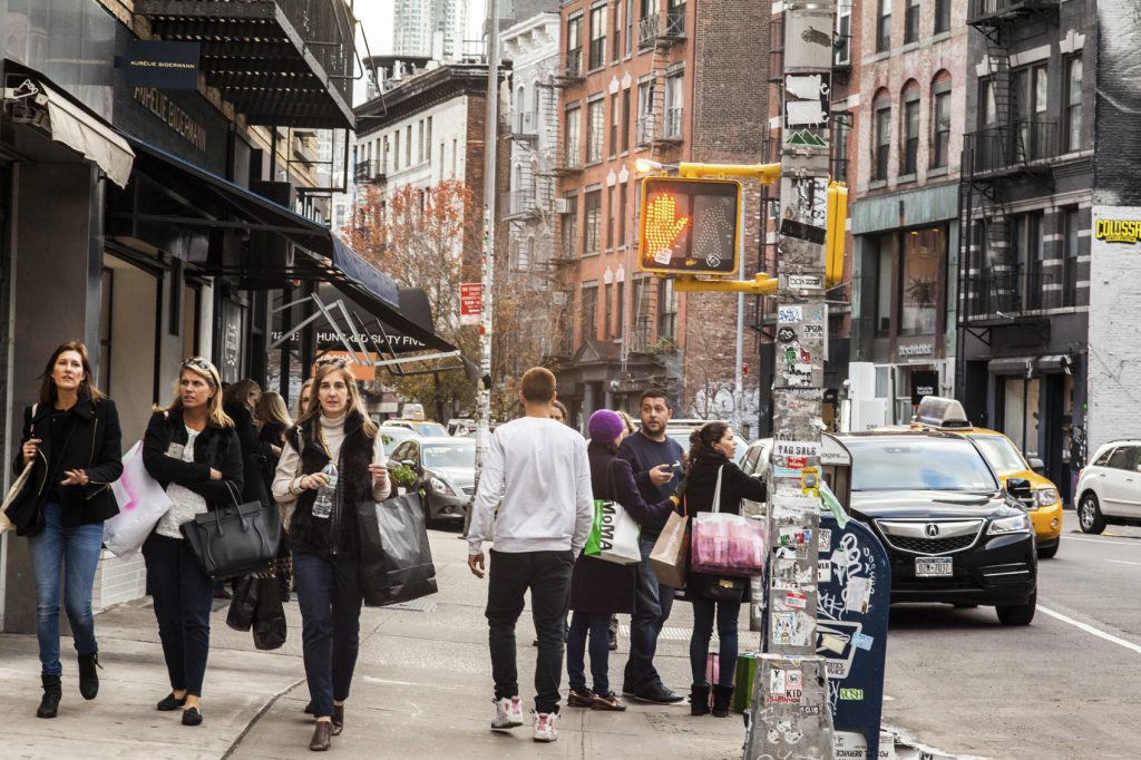 New York City, NY, USA - December 3, 2015: Pedestrians, locals, tourists on Lafayette street. Women with purses and shopping bags.