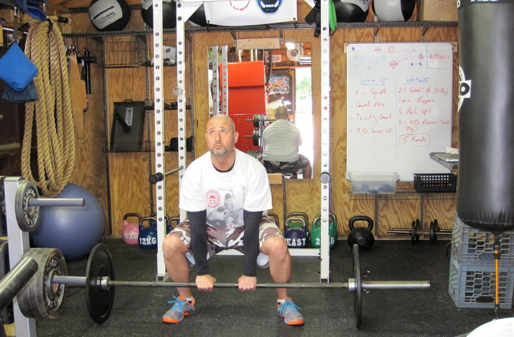 man squatting holding barbell with a narrow grip
