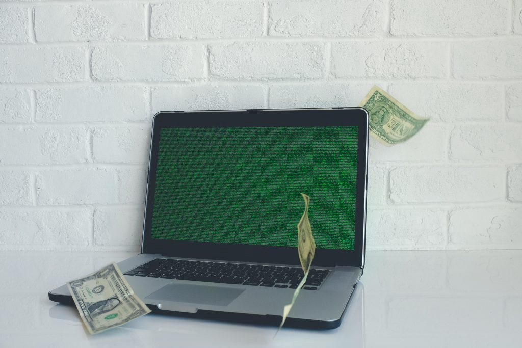 Growth Hacks being written in code on screen of a MacBook dollar bills floating around screen. Illusion of growth hack making instant money