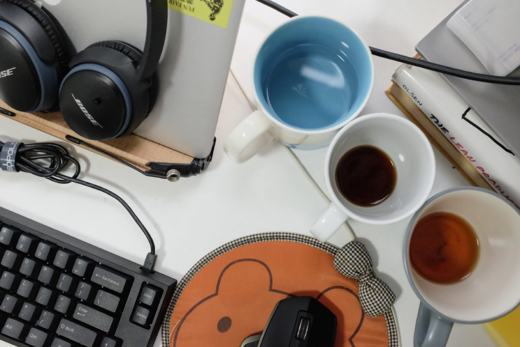 desktop filled with laptop and coffee mugs from working from home