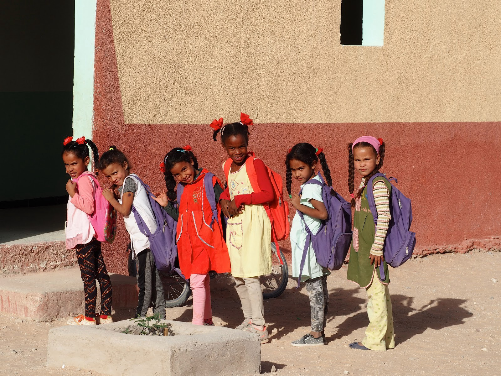 A group of school girls lines up to enter their classroom in Tindouf, Algeria. Classes are mixed with boys and girls, but they form separate lines to enter. The literacy rate in the Tindouf camps is reportedly over 90%, with girls' and boys' rates about the same. In FY 2018, PRM provided $6.9 million to UNHCR to support its work in Algeria. Photographer: Deputy Director for the PRM Africa Assistance Office Wendy Henning.