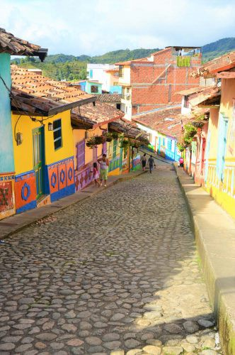 cobblestone street with brightly coloured houses guatape