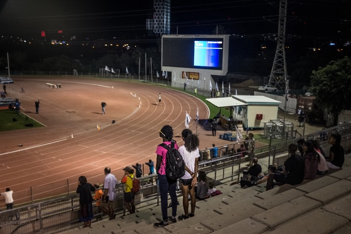 Athletes and asylum seekers Esteer Gabriel, from South Sudan (left), and Rahel Gebretsadik, from Eritrea (right), both 18 years old, watch their teammates compete at the National Sport Center Stadium in Tel Aviv, Israel.