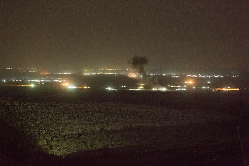 01/09/2015. Bashiqa, Iraq. A puff of smoke marks the spot where a coalition aircraft dropped a bomb on ISIS vehicles moving through the town of Bashiqa, Iraq. The ISIS heald city of Mosul can be seen illuminated in the background. Bashiqa Mountain, towering over the town of the same name, is now a heavily fortified front line. Kurdish peshmerga, having withdrawn to the mountain after the August 2014 ISIS offensive, now watch over Islamic State held territory from their sandbagged high-ground positions. Regular exchanges of fire take place between the Kurds and the Islamic militants with the occupied Iraqi city of Mosul forming the backdrop. The town of Bashiqa, a formerly mixed town that had a population of Yazidi, Kurd, Arab and Shabak, now lies empty apart from insurgents. Along with several other urban sprawls the town forms one of the gateways to Iraq's second largest city that will need to be dealt with should the Kurds be called to advance on Mosul.