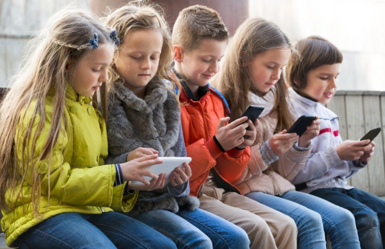 Kids sitting with mobile devices in street. Pic: iStock/JackF