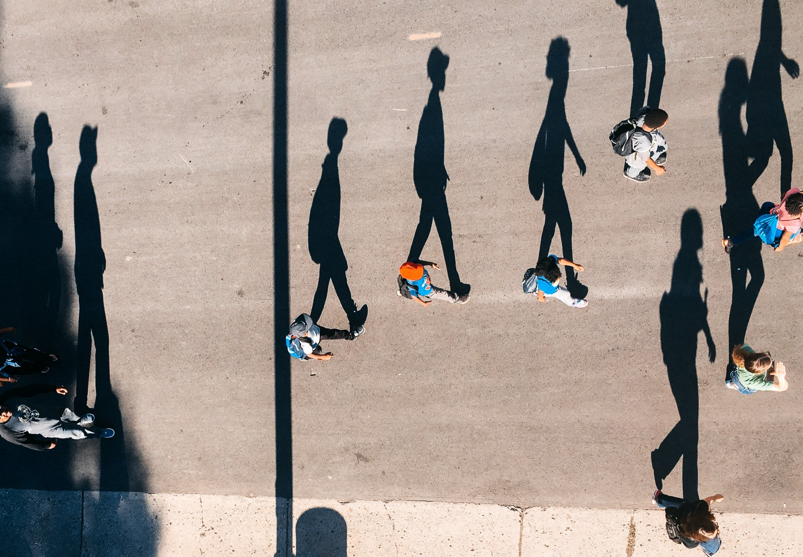 This image is meant to describe conformity. As the article leads you on a path of working out the identity you want and choosing that. The picture shows a top-down view (probably from a drone) of a stream of people walking left to right. The sun must be low as their shadows spread out beside them. It appears as a two dimensional image of shadows walking  in a line.