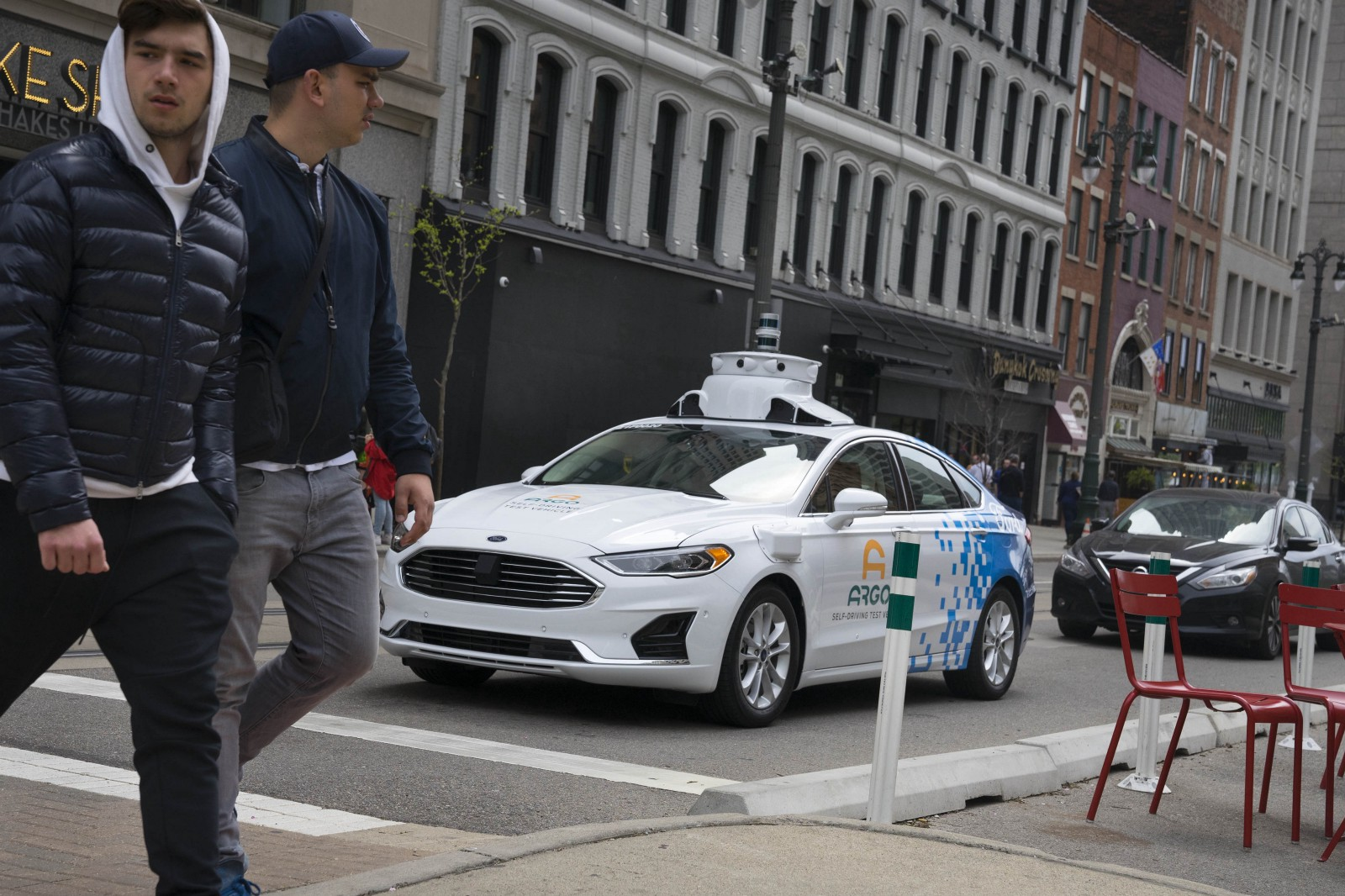 Pedestrians cross in front of a stopped Argo AI self-driving test vehicle in Detroit, MI, in June 2019.