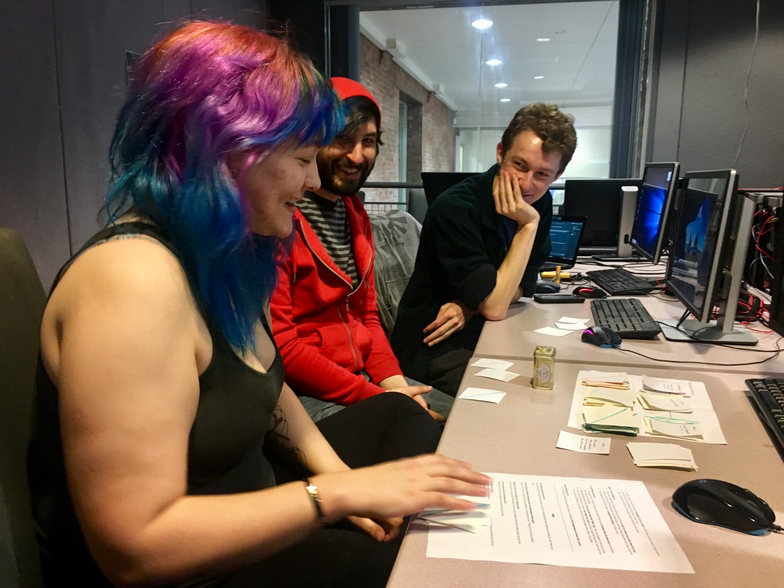An early playtest where players laugh as they play using index cards and a computer print-out of the rules.